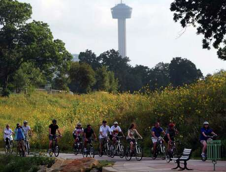 County officials on a bicycle tour pass wildflowers growing on the Mission Reach portion of the San Antonio River on June 2, 2011. Photo: JOHN DAVENPORT, Express-News File Photo / SAN ANTONIO EXPRESS-NEWS (Photo can be sold to the public)