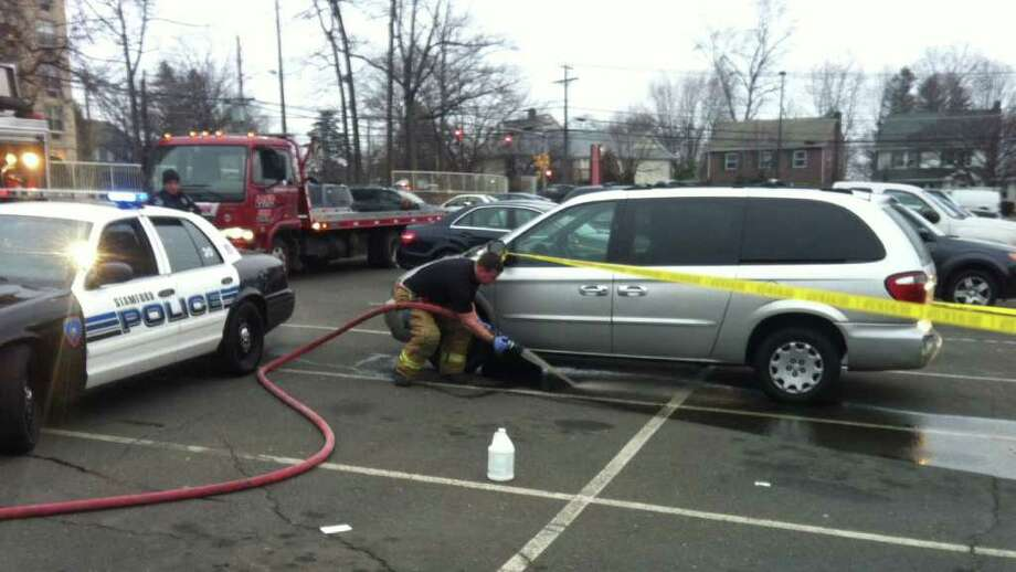 Firefighters rinsing blood from the parking lot at the Tully Medical Center parking lot where a man who had been stabbed came for medical treatment early this morning. The man arrived at the health center in the sliver minivan. Photo: John Nickerson