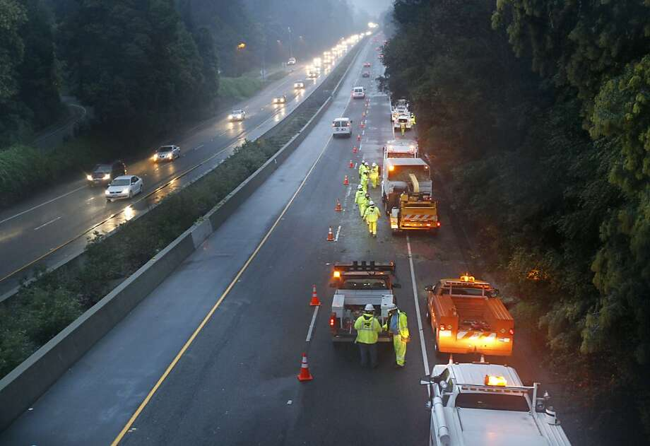 One lane of southbound Highway 13 remained closed as a Caltrans crew removes trees following a fatal early morning accident in Oakland, Calif. on Thursday, March 15, 2012. After a tree struck a car traveling southbound at the Park Boulevard exit, a truck driving behind the car then hit and killed one of the four passengers, who were all standing in the shoulder outside of the disabled car. Photo: Paul Chinn, The Chronicle