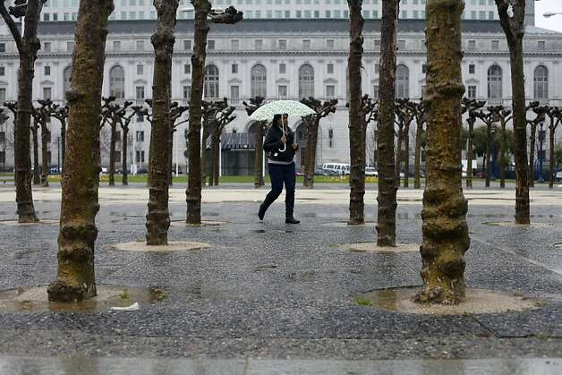 A woman walks through Civic Center as the rain continues to pour on Wednesday, March 14, 2012. Photo: Sean Culligan, The Chronicle