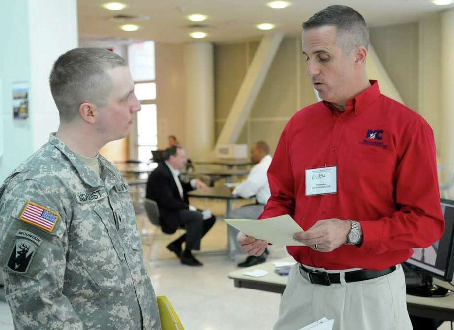 Army Specialist Brian Lindquist, left, speaks with Evan Eggers, Vice President of Marketing at Monument Construction LLC, at the GE jobs expo at the University of Connecticut's Stamford campus on Thursday, March 15, 2012. Photo: Lindsay Niegelberg / Stamford Advocate