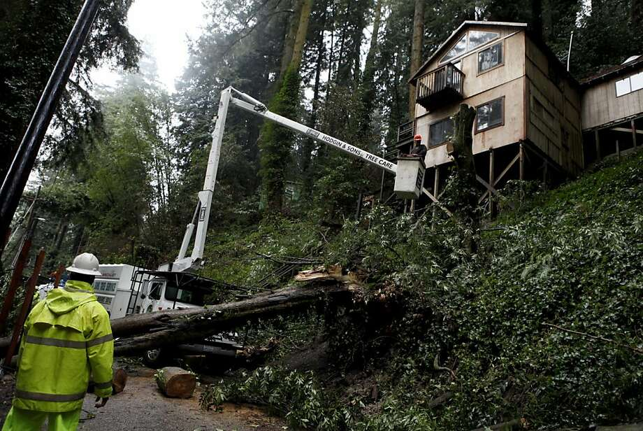 Members of the County of Sonoma Road Maintenance Division and Hodgin & Son Tree Service remove a bay tree that fell onto Starrett Hill Dr. and pushed three redwoods into a home in Monte Rio, California on Wednesday, March 14, 2012. A late winter storm has brought heavy rain and winds to Central and Northern California, flooding roads, downing trees and causing isolated power outages. And more rain is on the way over the next couple of days and the weekend, forecasters say, spelling good news for what has been an unusually dry winter. Photo: Beth Schlanker, Associated Press