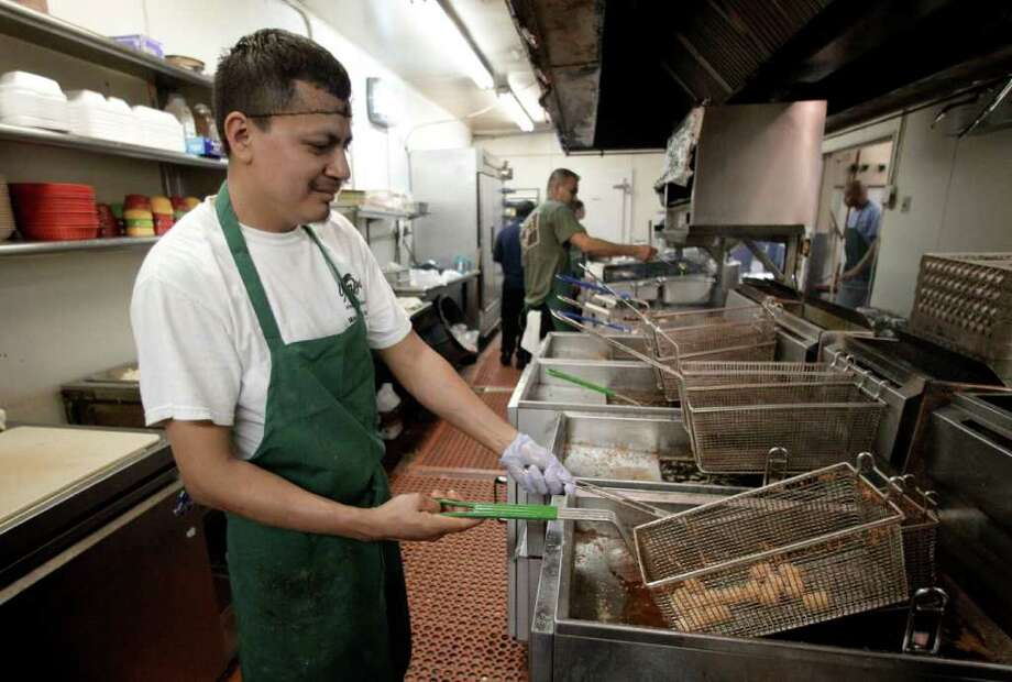 In this March 3, 2012 photo, George's restaurant employee David Lopez works on filling a customers order, in Waco, Texas. Fewer people sought unemployment benefits last week, adding to signs that the job market is strengthening. (AP Photo/Tony Gutierrez) Photo: Tony Gutierrez / AP