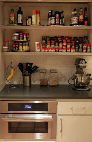 Condiments, herbs and spices are stored in an area with open cabinetry for easy access in Sharen Eggleston's kitchen. The area is out of view from the main entrance of the kitchen.  A built-in microwave finds a home below a caesarstone (cq) countertop. (Friday March 9, 2012) John Davenport/San Antonio Express-News Photo: SAN ANTONIO EXPRESS-NEWS