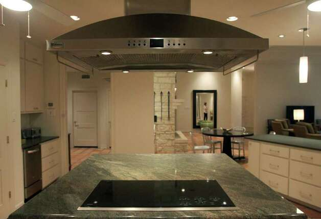 An island with a granite countertop houses a contemporary cooktop. A stainless vent hood hovers above, creating a central focal point in Sharen Eggleston's kitchen. (Friday March 9, 2012) John Davenport/San Antonio Express-News Photo: JOHN DAVENPORT, SAN ANTONIO EXPRESS-NEWS / SAN ANTONIO EXPRESS-NEWS (Photo cannot be sold to the public)