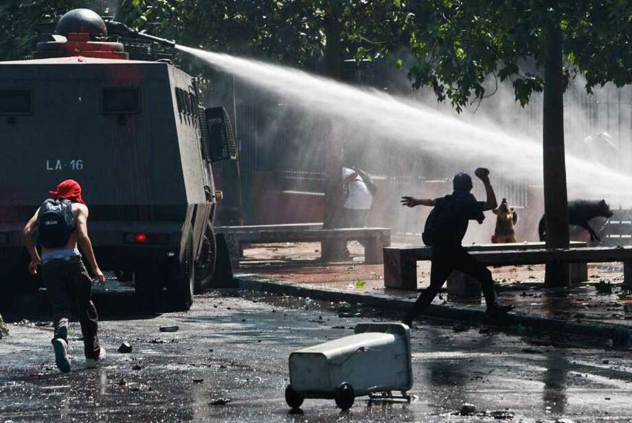 Police spray water during clashes with demonstrators at the year's first student protest in Santiago, Chile, Thursday March 15, 2012.  High school students are protesting for further educational reforms, saying their demands were not met after seven months of protesting in 2011. (AP Photo/Roberto Candia) Photo: Roberto Candia, Associated Press / AP