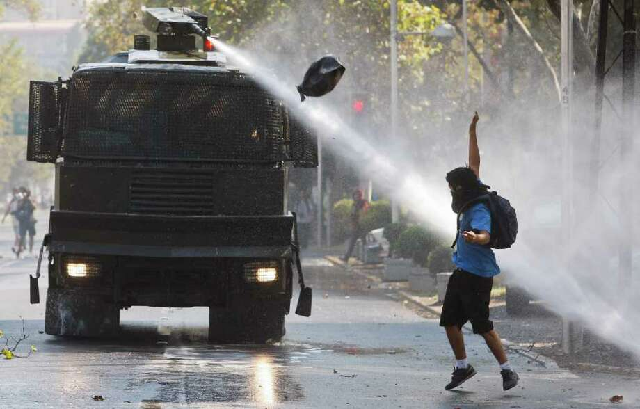 A police water canon vehicle sprays a demonstrator during the year's first student protest in Santiago, Chile, Thursday March 15, 2012.  High school students are protesting for further educational reforms, saying their demands were not met after seven months of protesting in 2011. (AP Photo/Roberto Candia) Photo: Roberto Candia, Associated Press / AP