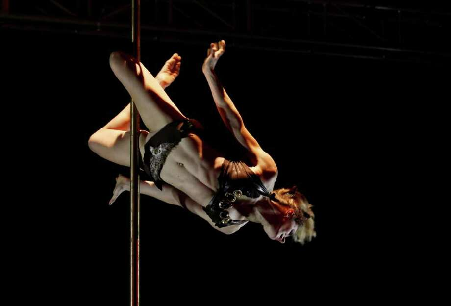French pole dancer Laurence Hilsum competes for the Women's Division at the International Pole Championship in Hong Kong Thursday, March 15, 2012.    (AP Photo/Kin Cheung) Photo: Kin Cheung, Associated Press / AP