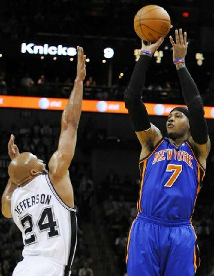 New York Knicks' Carmelo Anthony, right, shoots over San Antonio Spurs' Richard Jefferson during the first half of an NBA basketball game on Wednesday, March 7, 2012, in San Antonio. (AP Photo/Darren Abate) (AP)