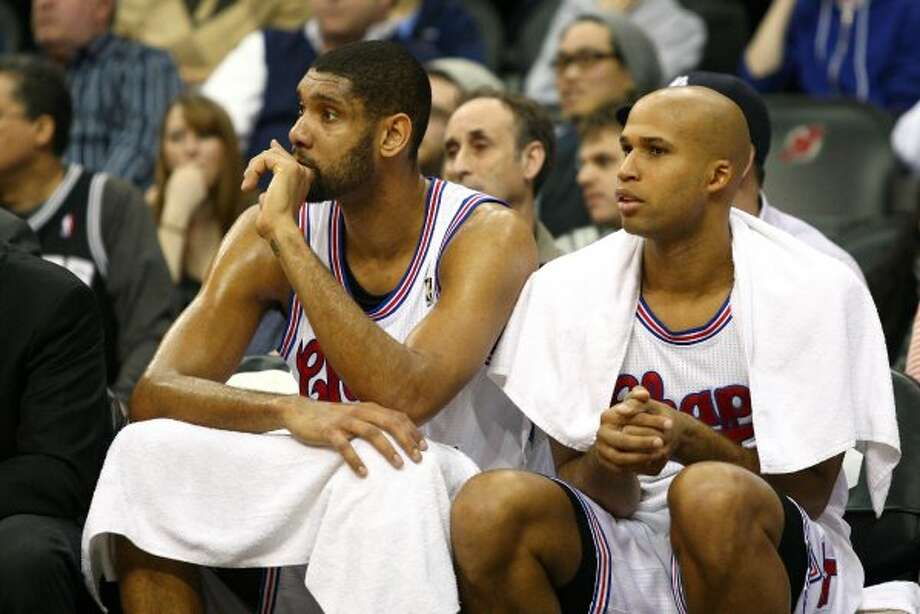 Tim Duncan, left, and Richard Jefferson look on from the bench during a San Antonio Spurs game against the New Jersey Nets in 2012 at Prudential Center in Newark, New Jersey.
