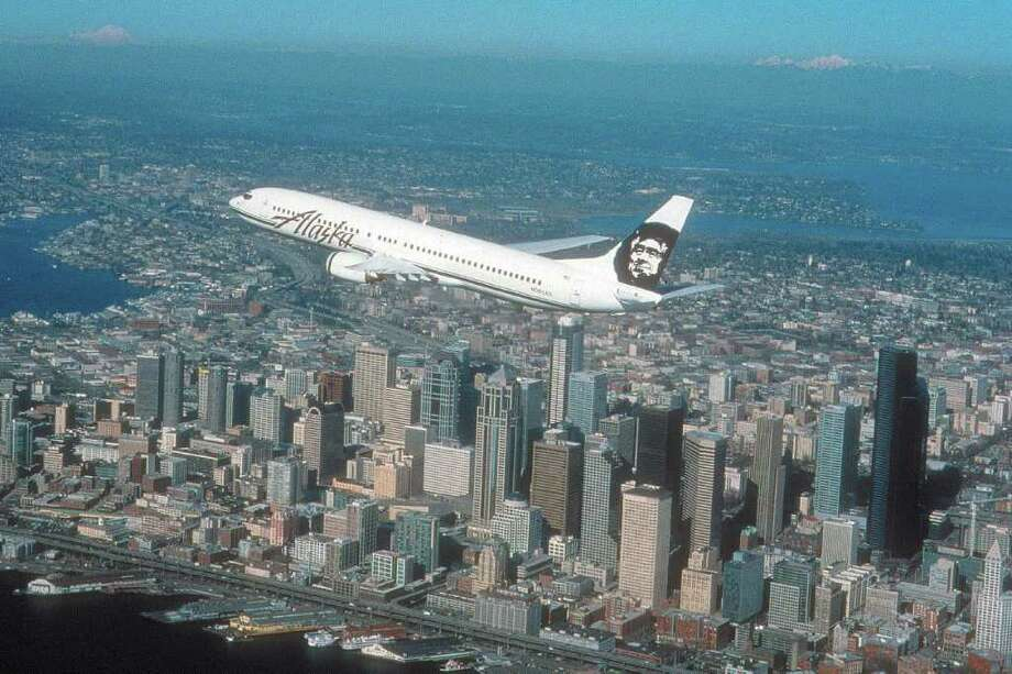 An Alaska Airlines Boeing 737-900 flies over downtown Seattle. Photo: Alaska Airlines