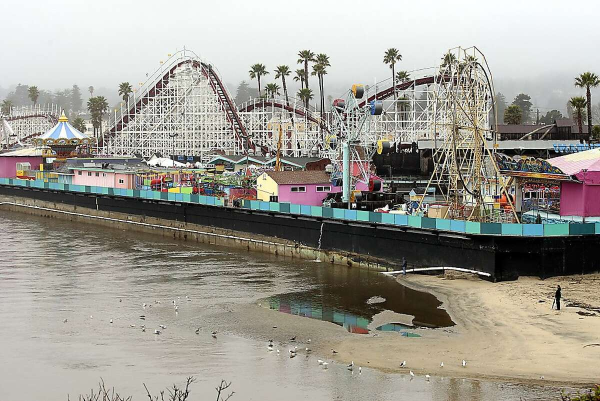 The rain-swollen San Lorenzo River threatens to undermine the historic Santa Cruz Beach Boardwalk in Santa Cruz, Calif., Thursday, March 15, 2012. A late winter storm that brought heavy rain and winds to Central and Northern California has led to at least one fatality and threatened flooding at the popular Santa Cruz Beach Boardwalk.