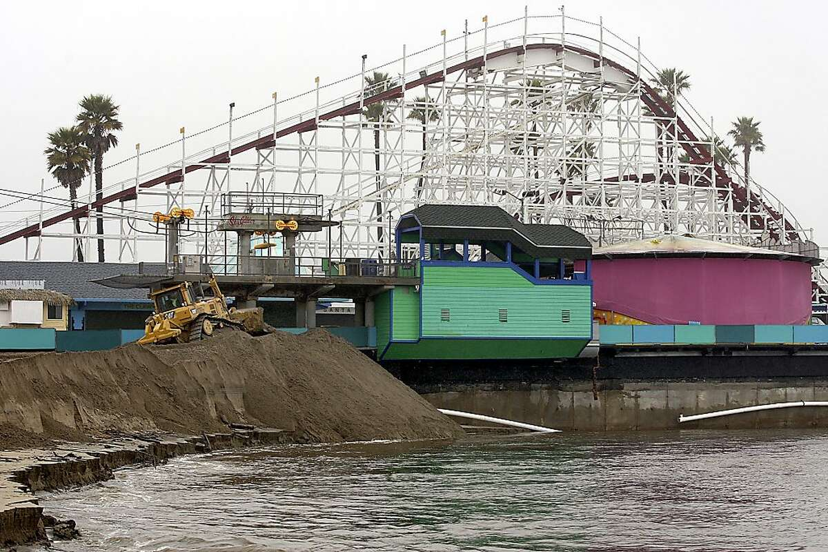 A bulldozer works to build a protective sand berm next to the historic Santa Cruz Beach Boardwalk in Santa Cruz, Calif., Thursday, March 15, 2012, as the rain-swollen San Lorenzo River threatens to undermine the seaside amusement park built in 1907. A late winter storm that brought heavy rain and winds to Central and Northern California has led to at least one fatality and threatened flooding at the popular Santa Cruz Beach Boardwalk. (AP Photo/Santa Cruz Sentinel, Dan Coyro)