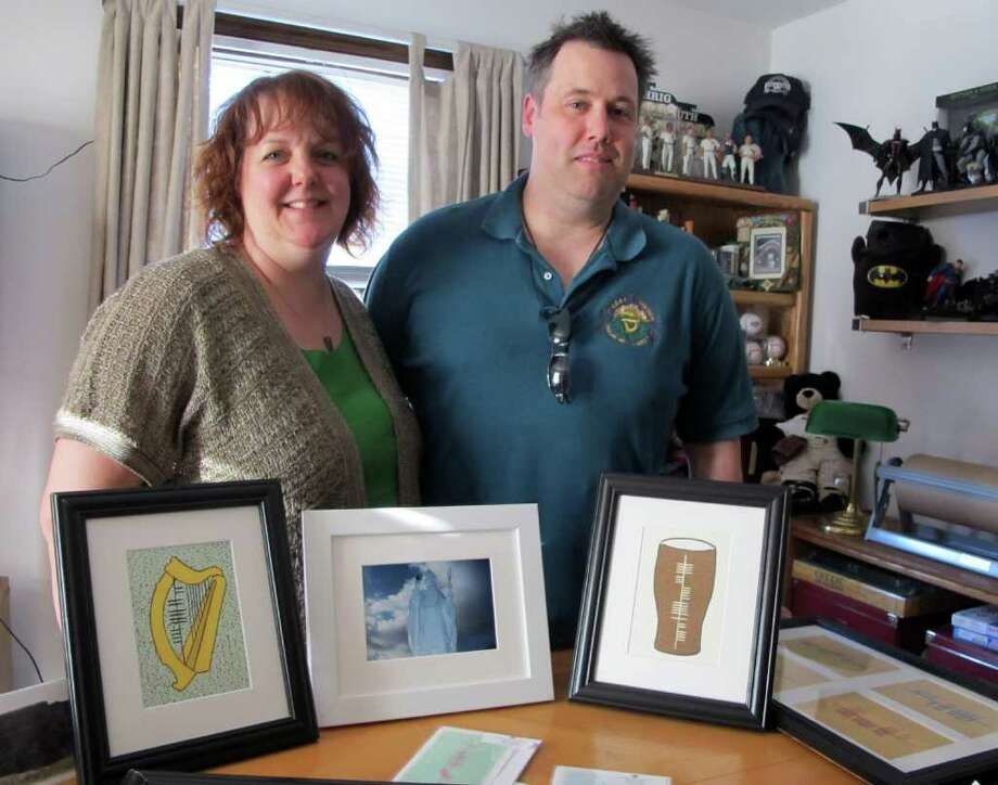 Ogham Art founders Christopher and Colleen Conway of Southington design custom jewelry, stationary, tattoos and prints displaying the ancient Irish alphabet, Ogham. Here the couple displays three of their products: the Irish Gaelic word for music, âÄúceolâÄù, painted inside a harp; the Irish Gaelic word for health, âÄúslainteâÄù, painted inside a pint glass; and a photograph of the statute of St. Patrick at the base of Croagh Patrick in County Mayo, Ireland. Photo: Brittany Lyte / Connecticut Post