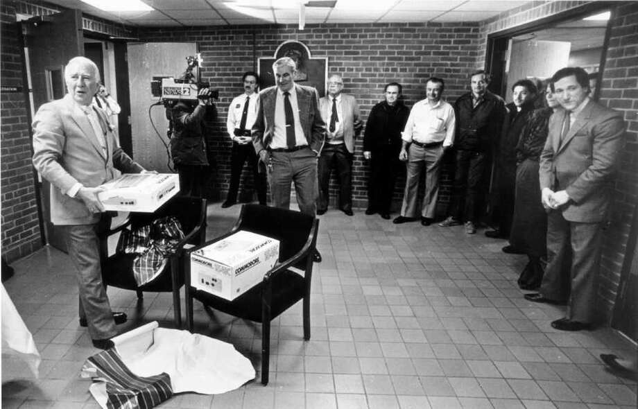 March 20, 1987: Retiring Stamford Police Chief John Considine finishes his last day. Here he opens a personal computer (a Commodore 1541C) he received from colleagues. Photo: File Photo