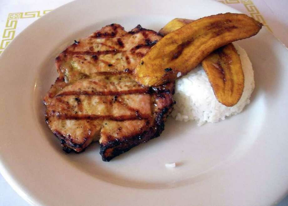 Pork loin and fried sweet plantains at El Pueblito Restaurant, 121 Wall St., Bridgeport. The pork is served with beans and rice. El Pueblito serves authentic Columbian food. Photo: Eileen Fischer / Connecticut Post