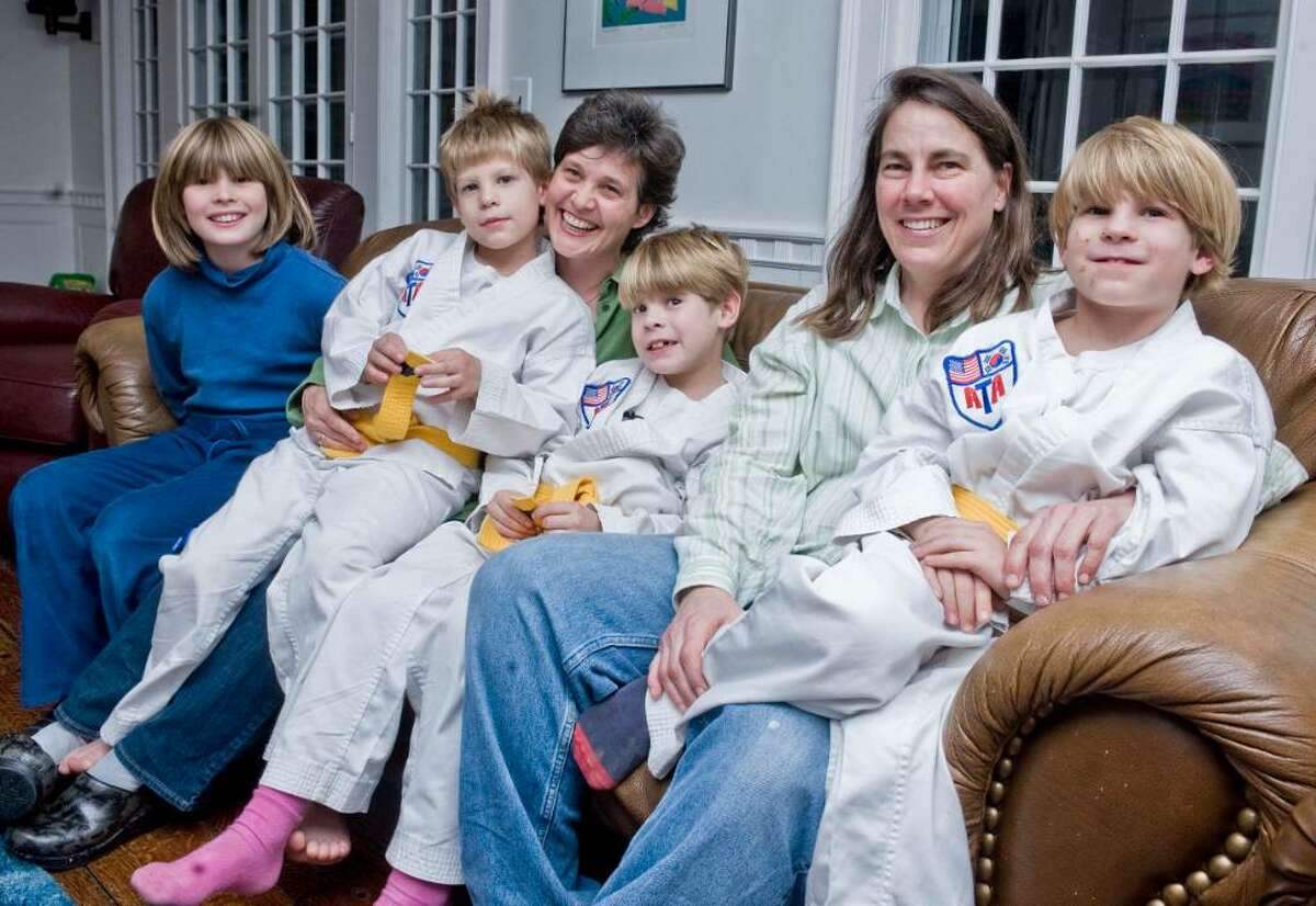 Robin Howell and Deborah Neumayer pose for a family photo in their Danbury home. From left, Emily Howell, 9, Tommy Howell, 7, Robin Howell, Aidan Howell, 7, Deborah Neumayer, Harrison Howell, 7.
