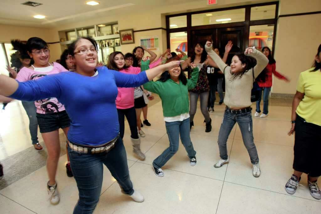 Students from Longfellow Middle School do jumping jacks during a physical  fitness portion of of the