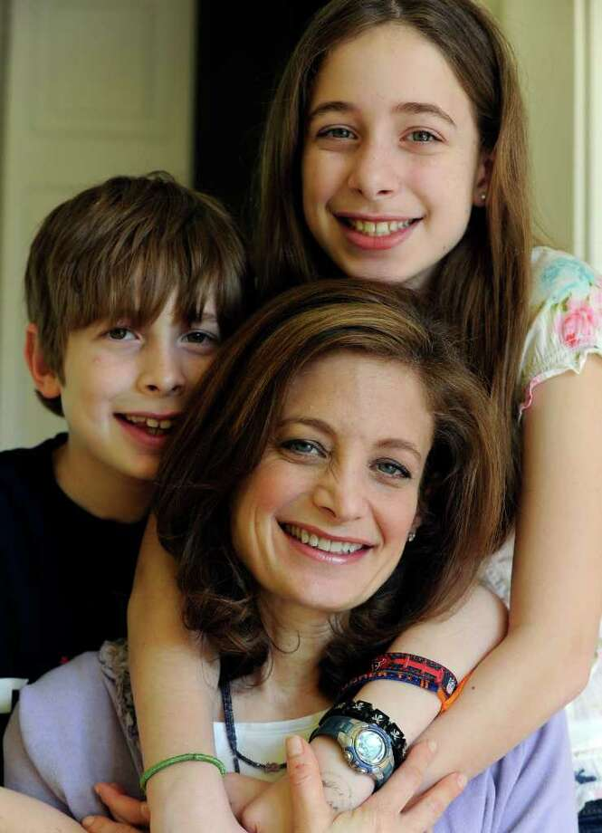 In this March 12, 2012 photo, Bettina Siegel, center, poses with her son Asher, 9, and daughter Lily, 12, at their home in Houston. Siegel, whose blog ?The Lunch Tray? focuses on kids? food, was so upset over a report of ammonia-treated meat trimmings in school lunches she started an online petition asking Agriculture Secretary Tom Vilsack to ?put an immediate end to the use of ?pink slime? in our children's school food.? As of Monday she had more than 175,000 online signatures. (AP Photo/Pat Sullivan) Photo: Pat Sullivan / AP