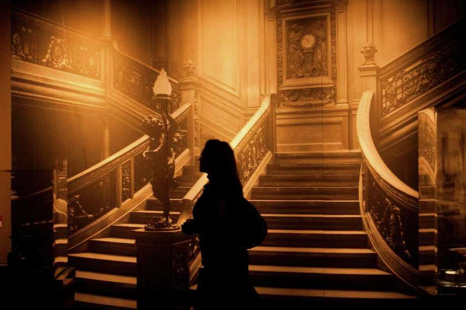 Cyndi Garcia walks past a picture of the famous grand staircase at Titanic: The Artifact Exhibition at the Houston Museum of Natural Science on Thursday March 15, 2012 in Houston, TX. Photo: J. Patric Schneider, For The Chronicle / Houston Chronicle