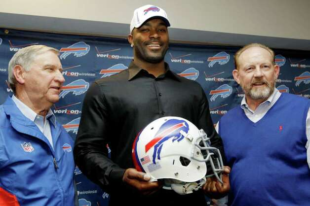 Buffalo Bills' Mario Williams, center, poses for a photo with Bills coach Chan Gailey, right, and Bills general manager Buddy Nix, left, after an NFL football news conference in Orchard Park, N.Y., Thursday, March 15, 2012. Williams signed a contract touted as the richest ever given to an NFL defensive player _ a deal worth up to $100 million with $50 million guaranteed, according to his agent, Ben Dogra. Photo: AP