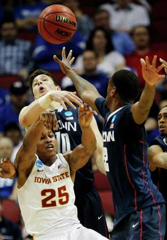 Iowa State guard Tyrus McGee (25) is guarded by Connecticut forward Tyler Olander (10) and forward Roscoe Smith (22) in the first half of their NCAA tournament second-round college basketball game in Louisville, Ky., Thursday, March 15, 2012. (AP Photo/Dave Martin) Photo: Dave Martin, Associated Press / AP