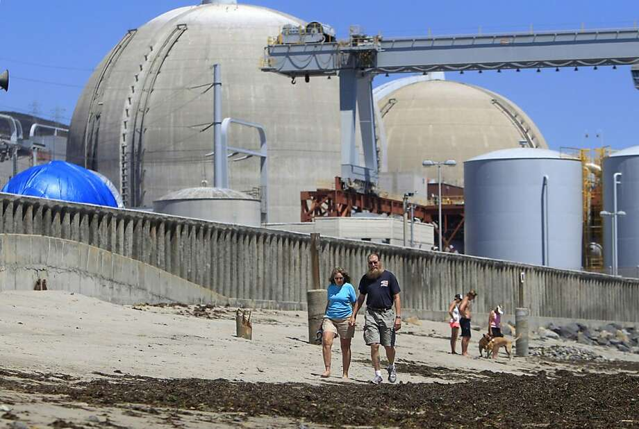 This file photo taken June 30, 2011, shows beach-goers walking on the sand near the San Onofre nuclear power plant in San Clemente,  Calif. Federal regulators are sending a special team to investigate the San Onofre nuclear power plant after tubes that carry radioactive water failed a pressure test. The Nuclear Regulatory Commission announced Thursday it will send an augmented inspection team to the northern San Diego County plant to review equipment design, construction and operation. Photo: Lenny Ignelzi, Associated Press