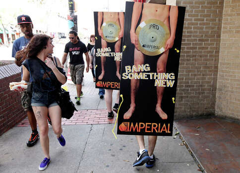 People look at Imperial Cymbals' ads as they walk along 6th Street during South by Southwest on March 15, 2012, in Austin. Photo: EDWARD A. ORNELAS, Edward A. Ornelas/Express-News / © SAN ANTONIO EXPRESS-NEWS (NFS)