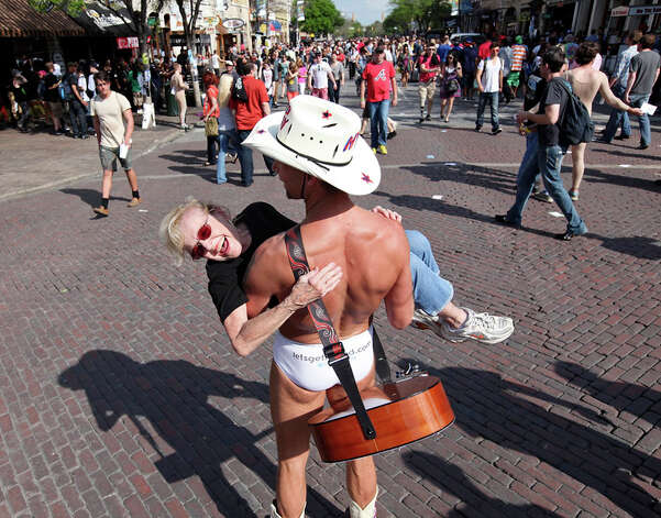 "Loretta Lang, 73, is all smiles as she is carried by Robert ""The Naked Cowboy"" Burck on 6th Street  during South by Southwest on March 15, 2012, in Austin. Photo: EDWARD A. ORNELAS, Edward A. Ornelas/Express-News / © SAN ANTONIO EXPRESS-NEWS (NFS)"