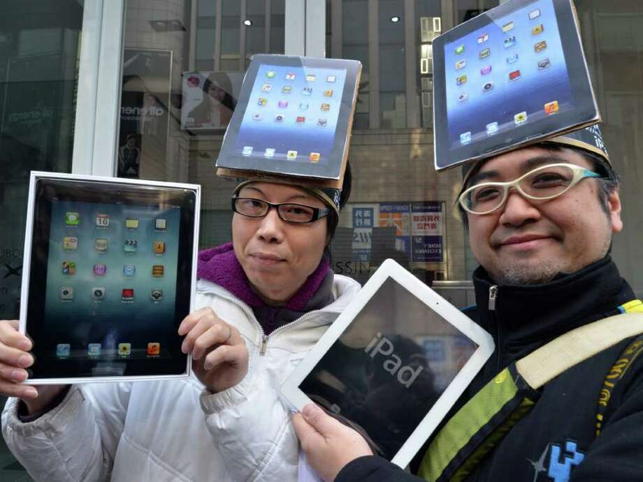 Japanese customers show off their newly purchased Apple's new iPads in Tokyo on March 16, 2010. Hundreds of gadget lovers queued up for the new IPads as a worldwide launch followed the global sunrise.  TOPSHOTS  AFP PHOTO / Yoshikazu TSUNO Photo: YOSHIKAZU TSUNO, AFP/Getty Images / AFP