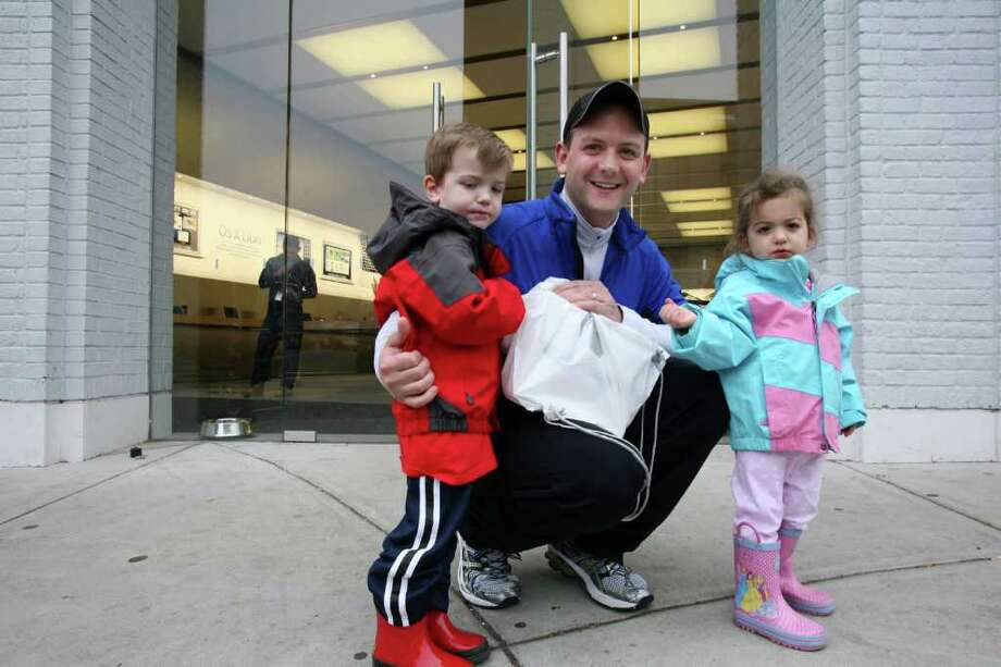 Michael Yardis of Greenwich and his two children Michael and Lily leave the Greenwich Avenue Apple store with one of the new Apple iPads Friday, March 16, 2012. Photo: David Ames / Greenwich Time