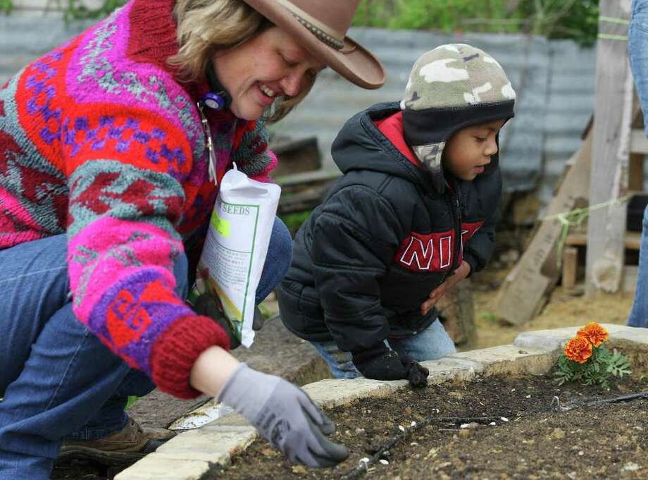 Cynthia Green, left, nutritionist with the Women, Infants and Children Program in Gonzales, gets help from Oscar Gamez, 3, while planting heirloom beans during a gardening class. Photo: Jerry Lara, San Antonio Express-News / © San Antonio Express-News
