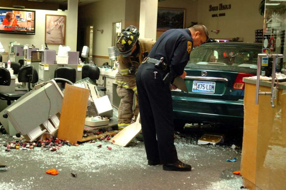A firefighter shovels up debri while a police officer takes notes after a car crashed into the Sun Nails salon in Milford, Conn. Thursday Nov. 12, 2009 injuring several people.
