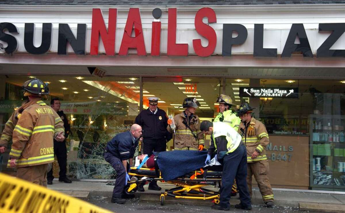 Paramedics strap a woman onto a gurney after a car crashed into the Sun Nails salon in Milford, Conn. Thursday Nov. 12, 2009 injuring several people.