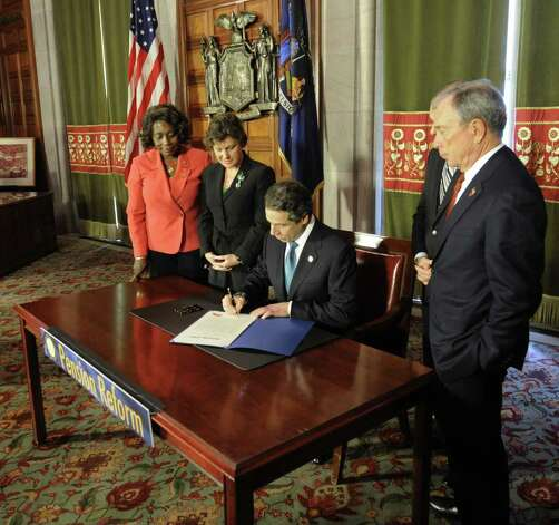 Gov. Andrew Cuomo signs the pension reform bill into law  in the Red Room of the State Capitol in Albany, N.Y. March 16, 2012.  The Governor is joined at the signing by Assemblymember Earlene Hooper, left Syracuse Mayor Stephanie Miner, Oneida County Executive Anthony Picente and New York City Mayor Michael Bloomberg, right. (Skip Dickstein/Times Union) Photo: Skip Dickstein / 2011