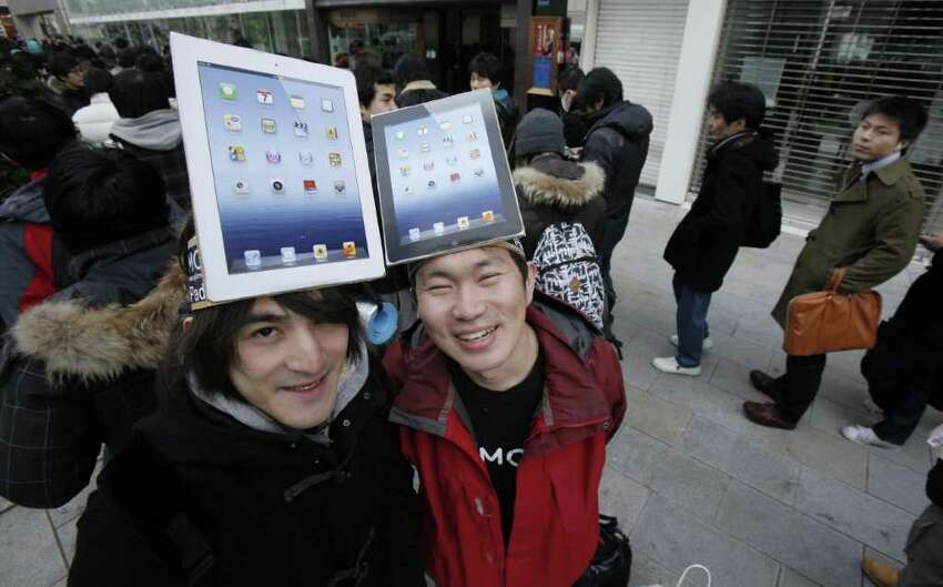 Tadashi Nagatani, left, and Nobuhiko Matsuba pose with mock-ups of iPad as customers stand in line near an Apple store before the latest iPad goes on sale, in Tokyo Friday, March 16, 2012. Sales of the third version of Apple's iPad began Friday morning in the country.
