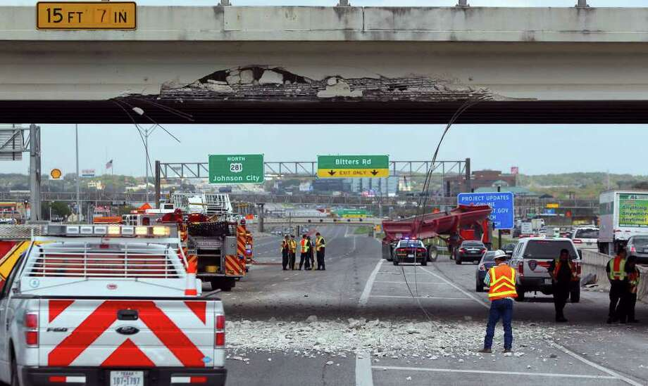 "Highway workers, emergency personnel and police work at the scene of U.S. 281 north at the Rhapsody drive bridge where a large gondola truck (red truck in background) struck the bridge at about 1:30 p.m. Friday March 16, 2012. Firefighters on the scene said nobody was injured. Northbound traffic on U.S. 281 was routed off the highway at the Nakoma street exit. Kevin Allen was driving behind the truck in his Nissan Ultima after having lunch when the truck struck the bridge. ""A wall of rock and dust came tumbling down. The truck hit the bridge and basically it exploded,"" Allen said. John Davenport/San Antonio Express-News Photo: JOHN DAVENPORT, SAN ANTONIO EXPRESS-NEWS / SAN ANTONIO EXPRESS-NEWS (Photo can be sold to the public)"