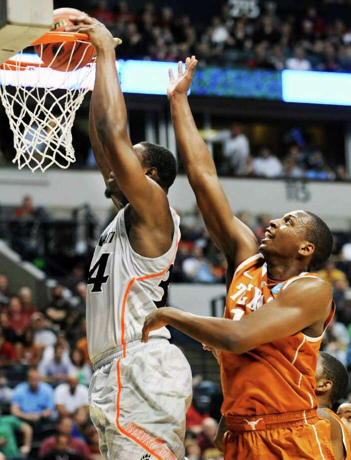 Texas' Jonathan Holmes (right), an Antonian product, is a step behind as Cincinnati's Yancy Gates gets a dunk. Photo: AP