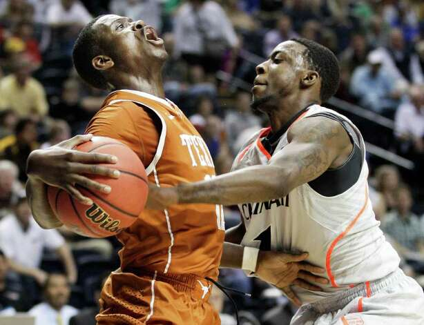 Texas guard Myck Kabongo, left, collides with Cincinnati guard Cashmere Wright, right, while driving to the basket in the first half of an NCAA college basketball tournament game on Friday, March 16, 2012, in Nashville, Tenn. Photo: AP