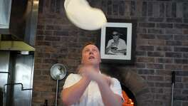 Chef Tyler Rodde tosses pizza dough toat Oenotri.