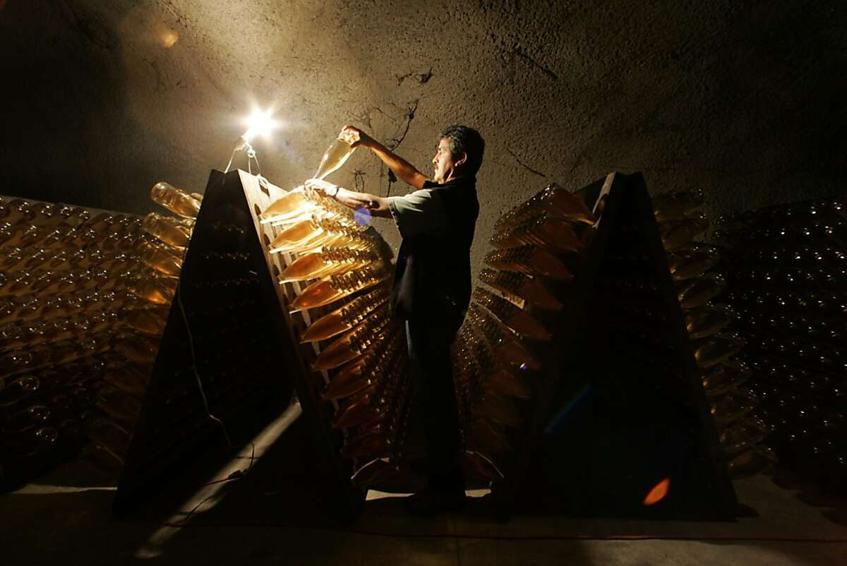 Ramon Viera, master riddler and 30-year-employee of Schramsberg, a maker of premium sparkling wine, examines bottles of 2002 Blanc de Noirs in the winery's deep and cool Diamond Mountain caves. Schramsberg is located at 1400 Schramsberg Road, Calistoga.