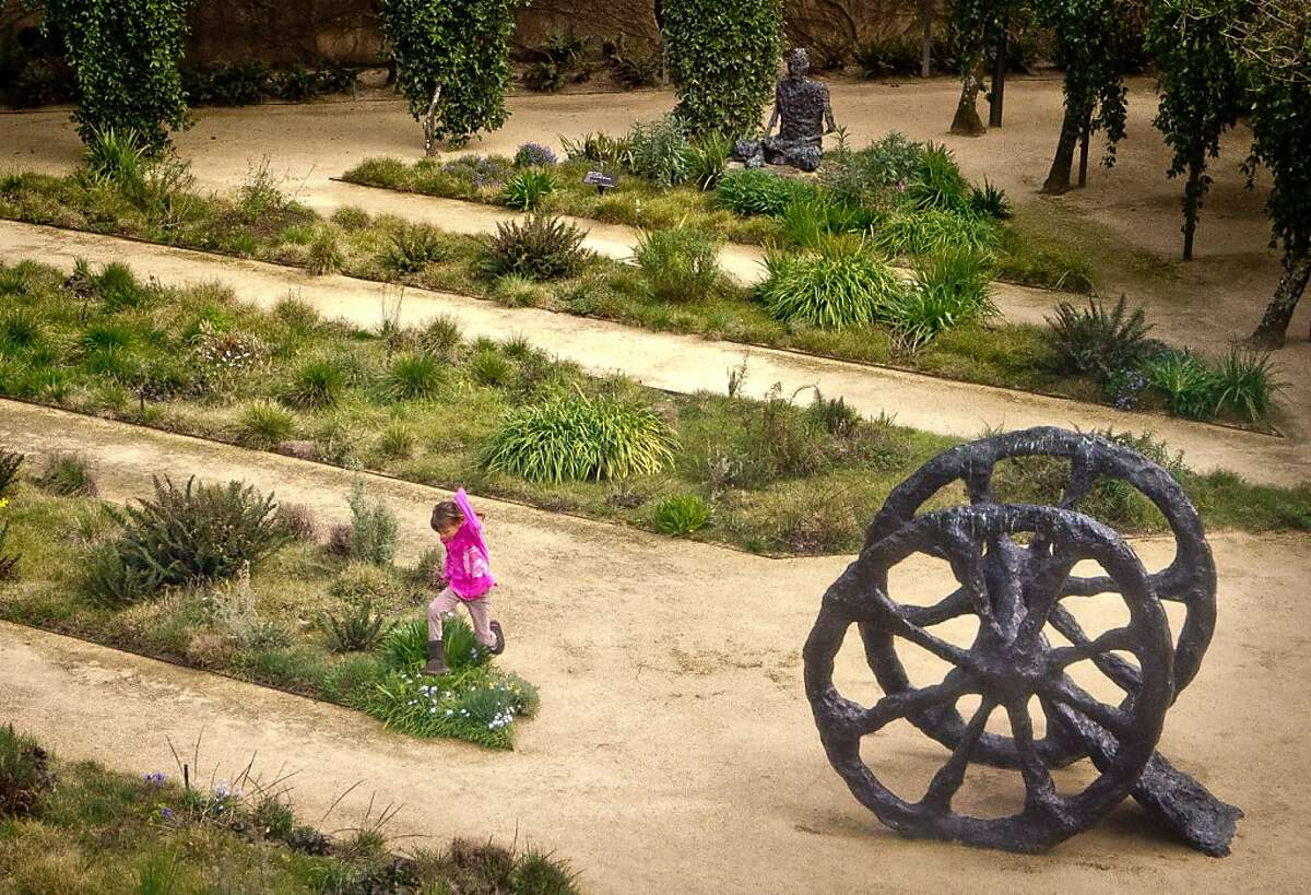 A little girl jumps over some flowers at the Hess Collection winery in Napa, Calif., on Saturday, March 10th, 2012.