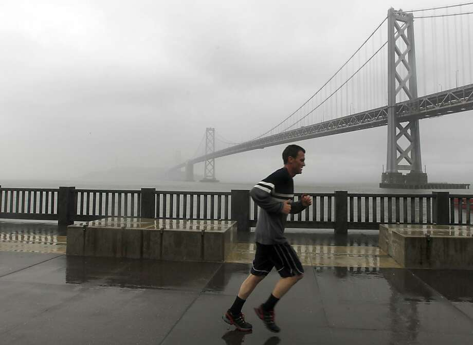 Friday's rainstorm doesn't stop a jogger from running past the Bay Bridge along The Embarcadero in San Francisco, Calif. on March 16, 2012. Photo: Paul Chinn, The Chronicle