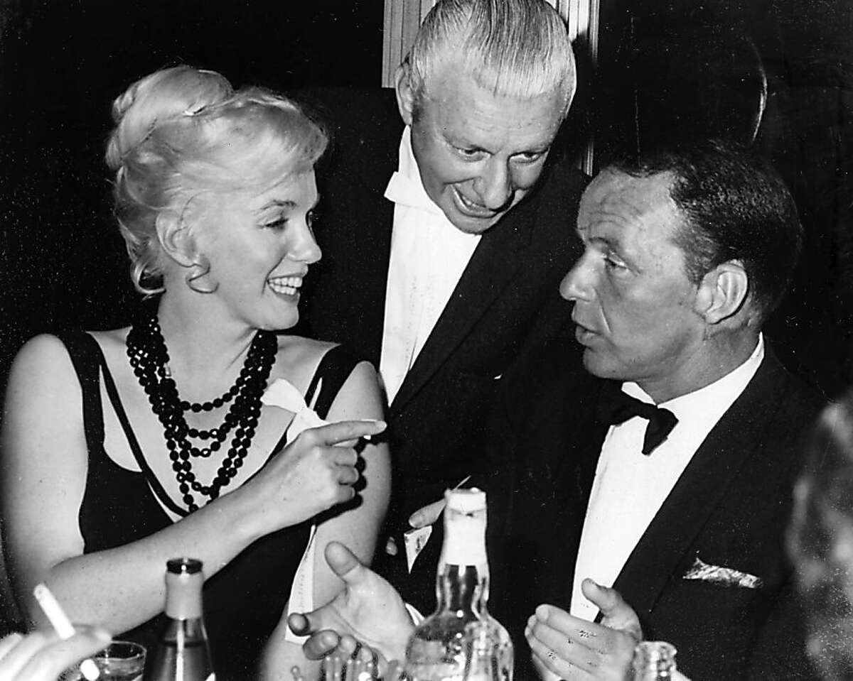 In this photo taken in 1959, Marilyn Monroe talks with Frank Sinatra while an unidentified man looks on at the Cal Neva Lodge in in Crystal Bay, Nevada.