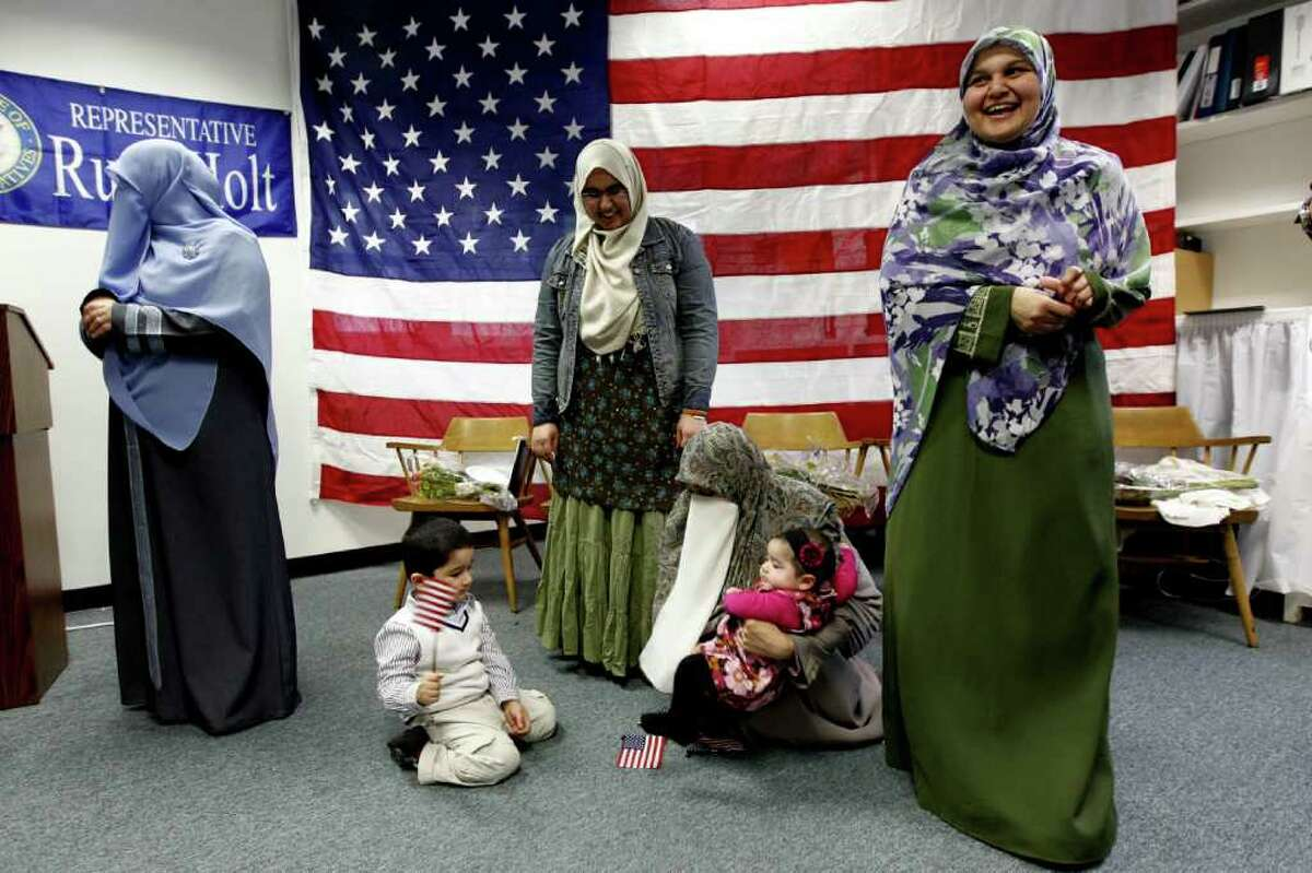 A jubilant Durree Hasan, right, became an American citizen Friday. Also naturalized were three of her daughters, Asna, left, Iqra and Nida, holding her daughter, Hafsa, 6 months. Grandson Abdullah, 3, waves the Stars and Stripes.
