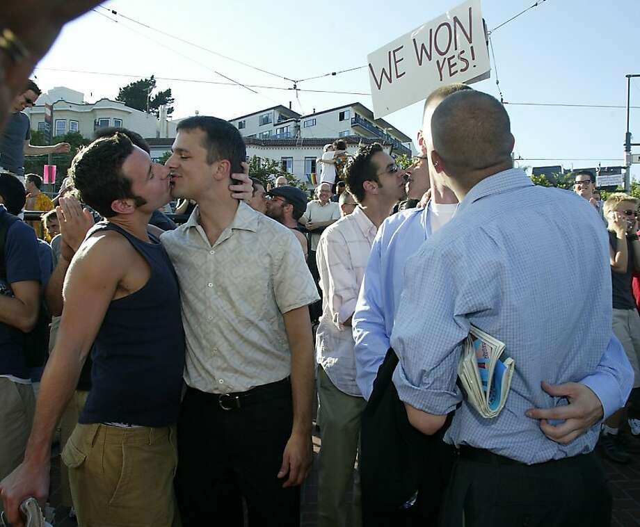 Gays and their allies gather at the corner of Castro and Market streets to celebrate a Supreme Court decision in Lawrence vs. Texas. left to right--Rod Speer (tank top) and Jake Schaaf (short sleeve), Adam Benditsky and Philip Gude, two couples kiss during a 'kiss in' ast Harvey Milk Plaza celebrating the decision. Shot on 6/26/03 in San Francisco. Photo: Liz Hafalia, The Chronicle 2003