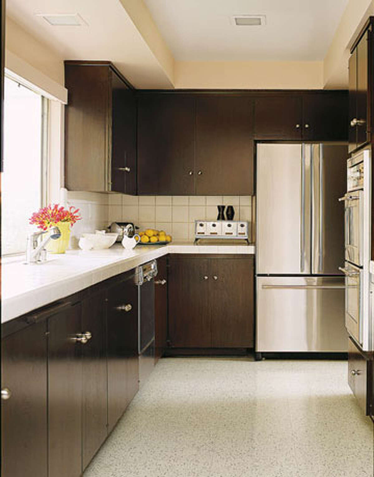 Love a streamlined look? Does clutter drive you crazy? You don't need to completely remodel to get European style. Designer Michael Berman renovated this kitchen by laying linoleum floor and staining the original walnut cabinets the color of black tea to set off the white tile of the countertops. Reprinted with Permission of Hearst Communications, Inc. Originally Published: What's Your Kitchen Style? John Coolidge