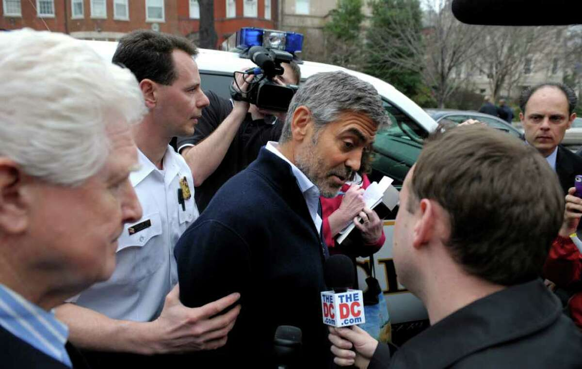 George Clooney, center, and Rep. Jim Moran, D-Va., left, are led to a police vehicle after being arrested during a protest at the Sudan Embassy in Washington.