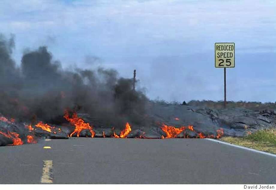 Lava from Kilauea Volcano observes the speed limit as it crosses, and shortens, the Chain of Craters Road in Hawai'i Volcanoes National Park around noon on Feb 13, 2003. STR: David Jordan Photo: David Jordan