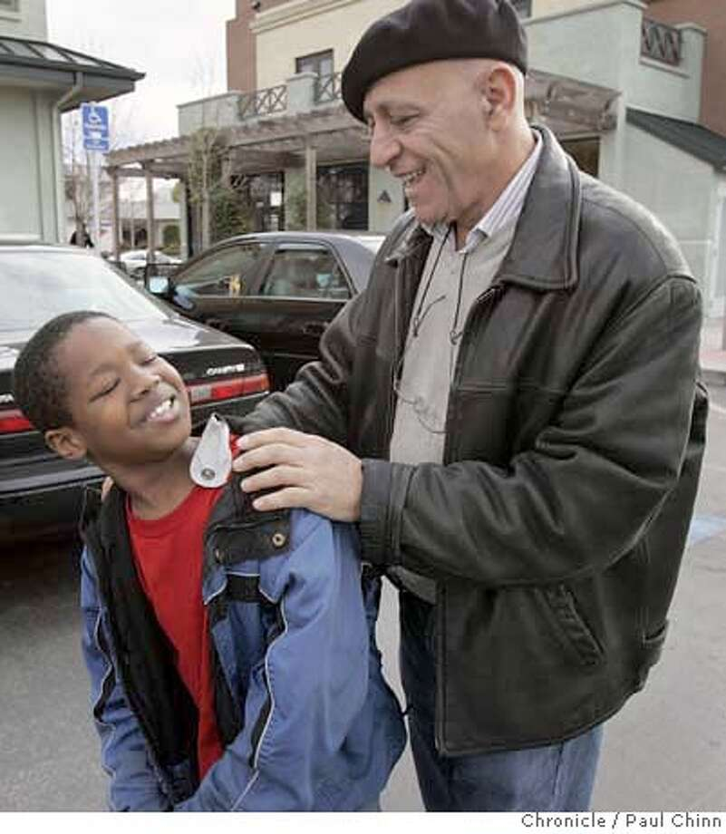 Abraham Oshana (right) and 10-year-old Xavier Dillard-Johnson spent the day together in Oakland, Calif. on Saturday, Dec. 16, 2006. Oshana is a mentor to Xavier through the OreMi (cq) program which connects mentors with children that have parents serving time behind bars.  PAUL CHINN/The Chronicle  **Abraham Oshana, Xavier Dillard-Johnson MANDATORY CREDIT FOR PHOTOGRAPHER AND S.F. CHRONICLE/ - MAGS OUT Photo: PAUL CHINN